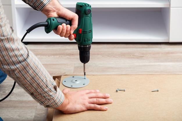Processo di assemblaggio di mobili, il maestro raccoglie mobili da tavolo utilizzando lo strumento trapano traslochi, migliorie, ristrutturazioni di mobili.