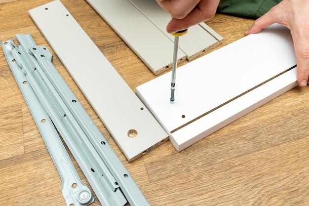 Processo di assemblaggio dei mobili, avvitamento dei raccordi con un cacciavite