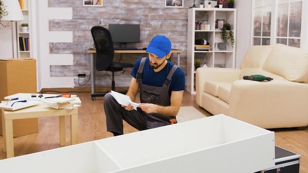 Addetto all'assemblaggio di mobili che utilizza le istruzioni di consultazione del cacciavite.