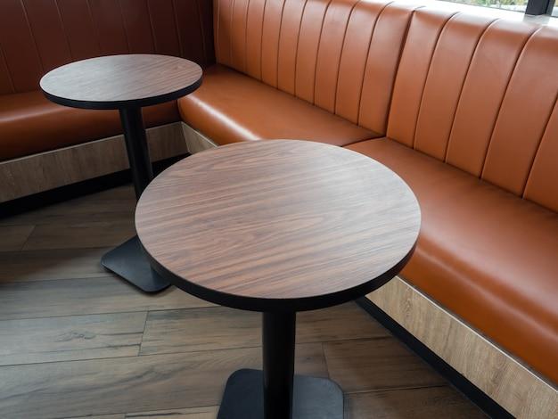 Decorazione di mobili in stile retrò cafe. barre di tavola di legno rotonde vuote e sofà di cuoio lungo arancio sul pavimento di legno.