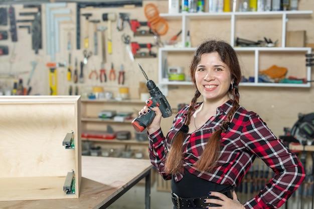 Fabbrica di mobili, piccole imprese e concetto di lavoratrice - donna con un trapano in fabbrica.