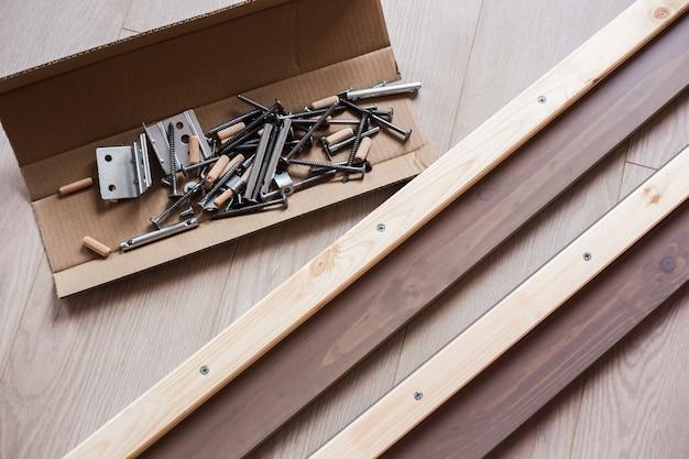 Accessori per mobili, viti e altre parti in una scatola artigianale aperta sul pavimento, montaggio di mobili a casa.