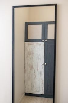 Mobili, guardaroba. armadio di design con anta in bianco e nero e superficie opaca, in piedi contro il muro, riflesso nello specchio