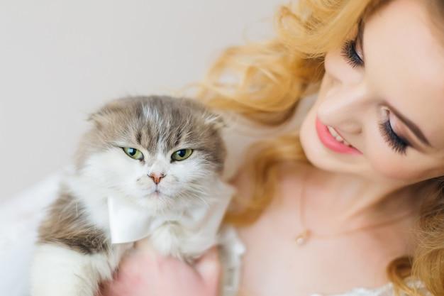 Gatto peloso con farfallino guarda nella telecamera e la sposa tiene la vista dall'alto del gatto