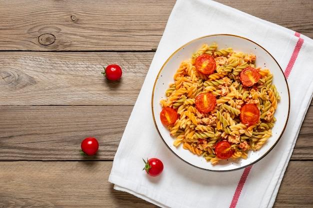 Fusilli - pasta italiana classica, carne di pollo, pomodorini, basilico in salsa di pomodoro in una ciotola bianca