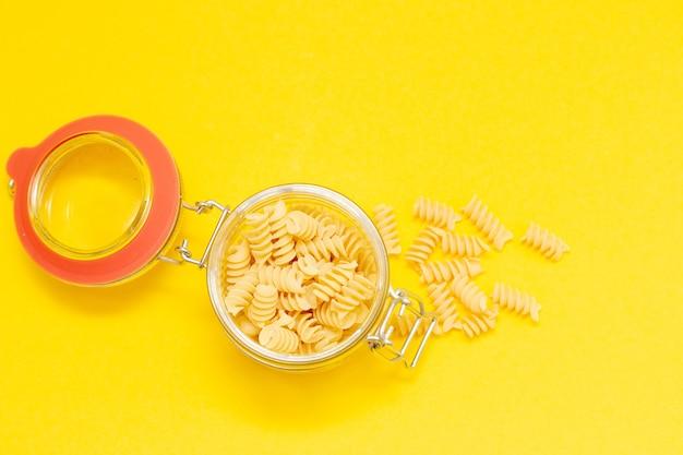 Maccheroni della pasta dei fusilli in vaso di vetro aperto su un colore giallo