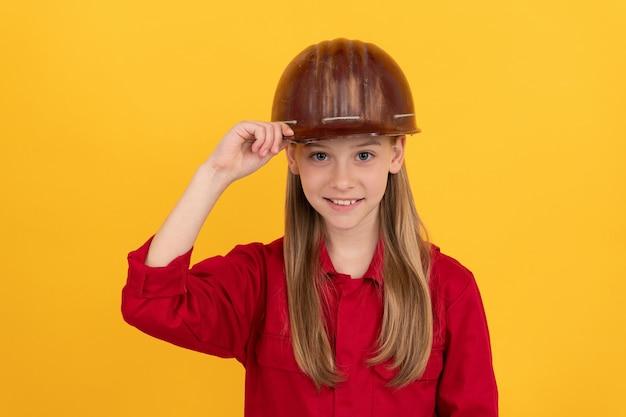 Carriera futura di una ragazza adolescente nel costruttore di caschi con il concetto di sviluppo dell'infanzia, felice festa del lavoro.