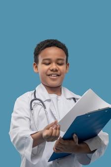 Futuro dottore.. gioioso ragazzo afroamericano in camice guardando fogli di carta nella cartella blu in piedi in studio fotografico