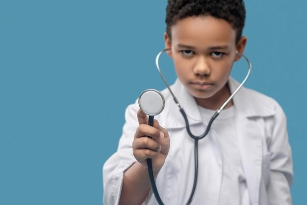 Futuro dottore. tubo dello stetoscopio nelle mani di un ragazzo dalla pelle scura premuroso in camice bianco in piedi su sfondo blu