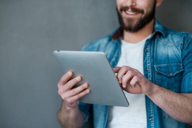 Il futuro è nel tocco. immagine ritagliata di un giovane che tiene in mano un tablet digitale e sorride mentre è in piedi su uno sfondo grigio