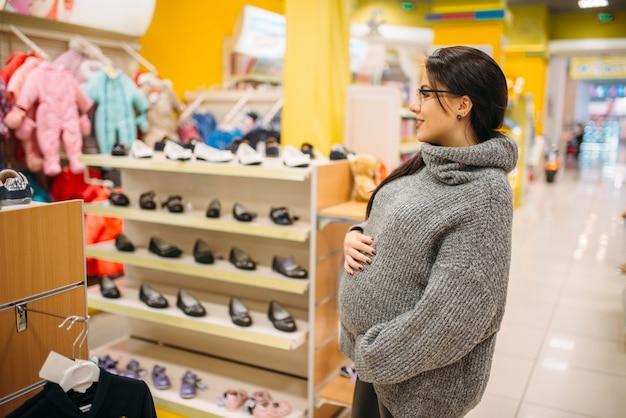 Futura mamma nel negozio per bambini e neonati, reparto calzature.