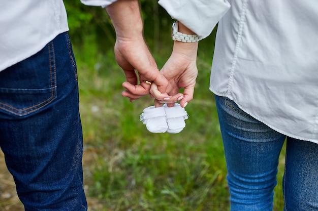 Futuri genitori che tengono piccole scarpe