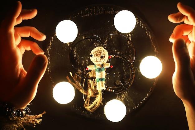 Futuro cassiere. natura morta mistica con bambola voodoo, tarocchi, libri, candele malvagie e oggetti di stregoneria. rito di divinazione.