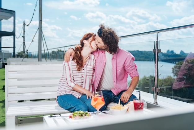 Futura moglie. uomo barbuto riccio che bacia la sua futura moglie con una cena romantica sulla splendida terrazza estiva