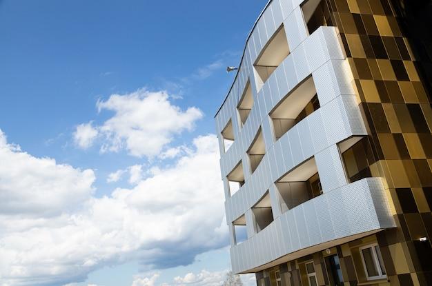 Facciata dell'edificio futuristico con rilievo traforato per la zona del balcone del salone e superficie colorata marrone piastrellata