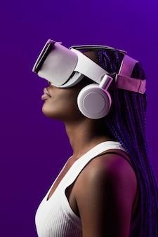 Futuristico vista laterale ritratto di giovane donna afro-americana che indossa l'auricolare vr su sfondo viola