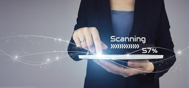 Concetto di scansione futuristico e tecnologico. compressa bianca in mano di donna d'affari con segno di scansione ologramma digitale su sfondo grigio.