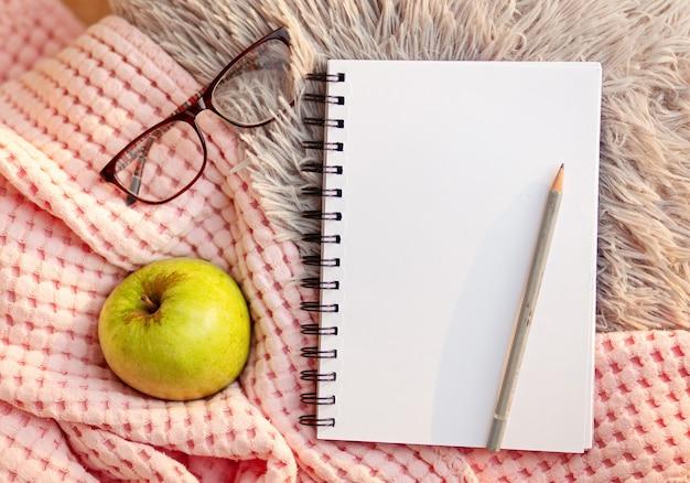 Plaid di pelliccia grigia sfocata e quaderno bianco con copertina rosa, elma, occhiali. lay piatto, vista dall'alto, copia spazio. atmosfera accogliente