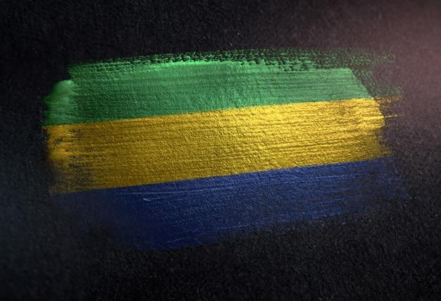 Bandiera del gabon fatta di vernice pennello metallico sulla parete scura del grunge