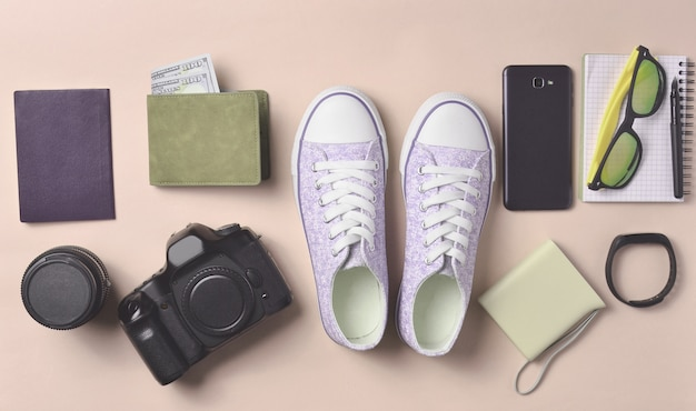 Layout di gadget e accessori su uno sfondo rosa pastello. scarpe da ginnastica, attrezzatura fotografica, borsa con dollari, smartwatch, smartphone, notebook, occhiali da sole