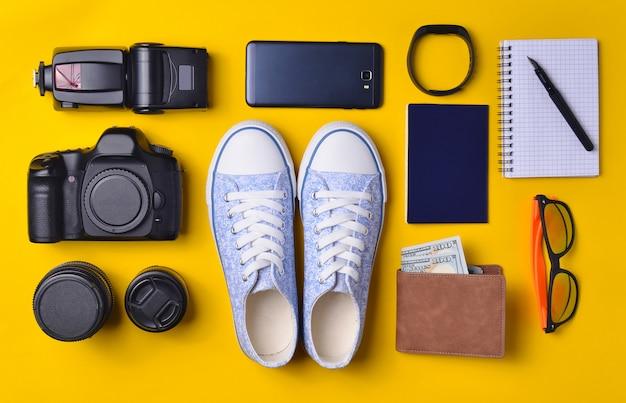 Layout di gadget e accessori su uno sfondo giallo. scarpe da ginnastica, attrezzatura fotografica, borsa con dollari, smartwatch, smartphone, notebook, occhiali da sole. il concetto di viaggio, oggetti, vista dall'alto