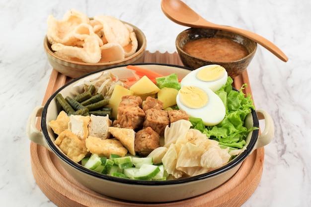 Insalata mista indonesiana gado gado di verdure bollite o al vapore servita con salsa di arachidi. gado-gado siram popolare a giacarta fatto con patate, tempeh, tofu, germogli, carote, fagioli lunghi e uova