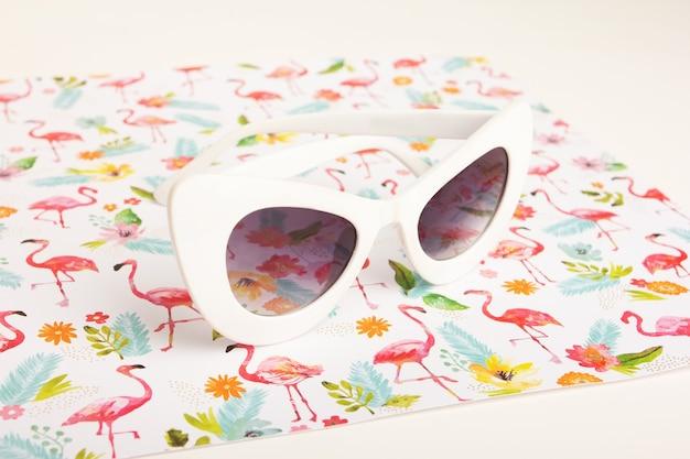 Gafas de sol blancas de moda sobre un fondo de flores