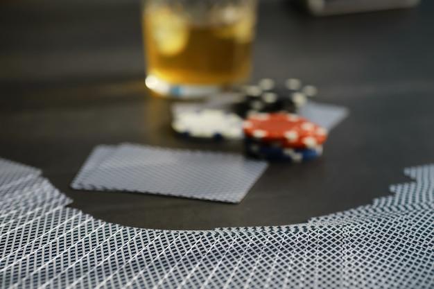 Giochi di carte per soldi. il poker in versione texas holdem. carte in mano, fiches da gioco, un mazzo di carte alcoliche in un bicchiere.