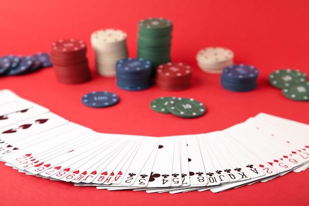 Chip di gioco e carte per il poker sulla parete rossa. vista dall'alto