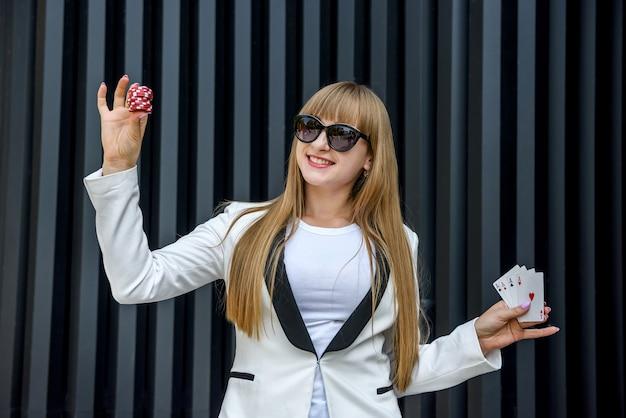 Concetto di gioco d'azzardo. bella donna in vestito bianco che tiene i chip di poker e le carte da gioco
