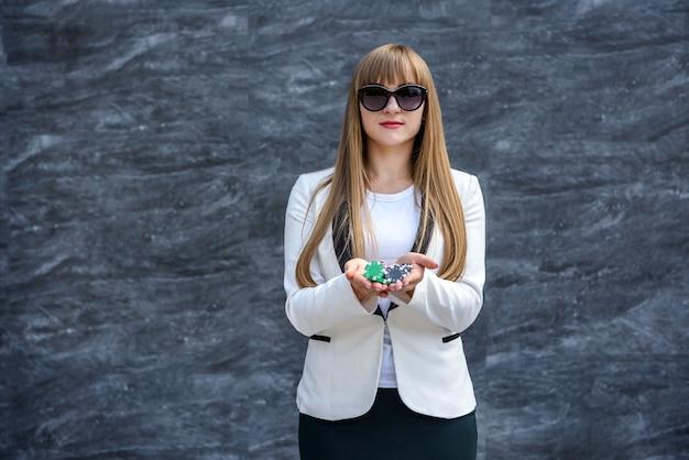 Concetto di gioco d'azzardo. donna d'affari in occhiali da sole che tiene fiches da poker e posa su sfondo astratto
