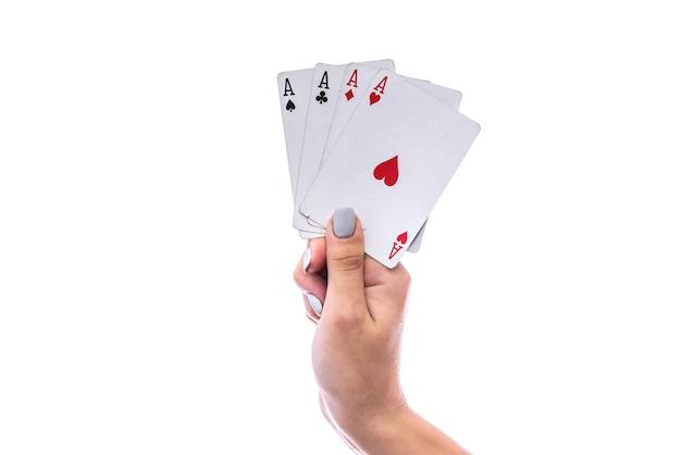 Concetto di gioco d'azzardo. mano femminile che tiene una combinazione di quattro assi isolati su bianco