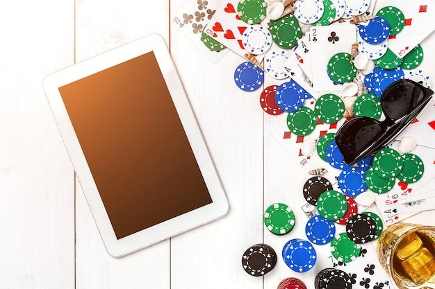 Carte da gioco d'azzardo con fiches da poker e dadi vicino al tablet sul tavolo in legno vista copyspace poker
