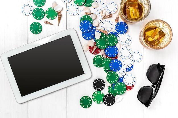 Carte da gioco d'azzardo con fiches da poker e dadi vicino al tablet sul piano del tavolo in legno vista copyspace poker