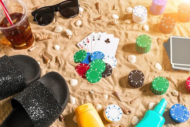 Gioco d'azzardo sul concetto di vacanza sabbia bianca con conchiglie colorate fiches da poker e carte vista dall'alto