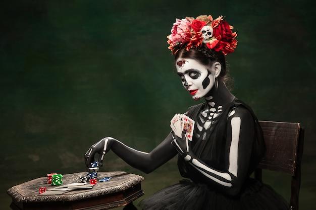 Gioco d'azzardo. ragazza giovane come la morte di santa muerte saint o il teschio di zucchero con trucco luminoso. ritratto isolato su sfondo studio verde scuro con copyspace. festeggiando halloween o il giorno dei morti.