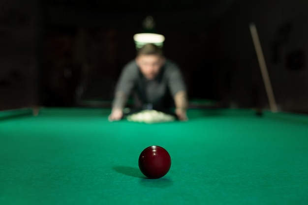 Gioco del biliardo. l'uomo mette le palle sul tavolo da biliardo verde.