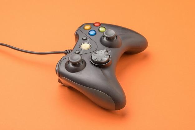 Una console di gioco su uno sfondo arancione brillante.