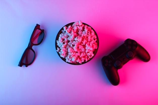 Gamepad, telecomando della tv, occhiali 3d e una ciotola di popcorn
