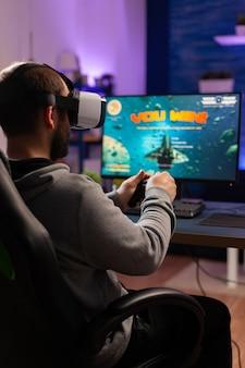 Giocatore che perde un torneo di sparatutto spaziale online indossando cuffie per realtà virtuale. esport man ubicazione sulla sedia da gioco a tarda notte in home studio utilizzando attrezzature professionali