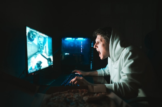 Il giocatore si siede a casa al tavolo davanti al computer e mangia la pizza