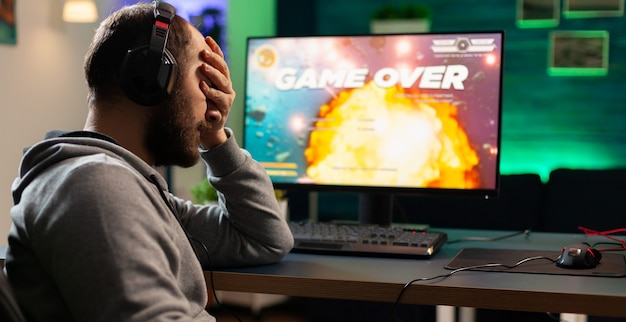 Giocatore con auricolare e microfono che perde videogiochi nello studio domestico di gioco e parla con gli amici in rete. uomo sconfitto con le cuffie che si esibiscono in streaming online durante il torneo