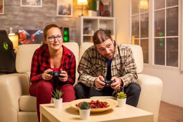 Coppia di giocatori che giocano ai videogiochi sulla tv con controller wireless in mano.