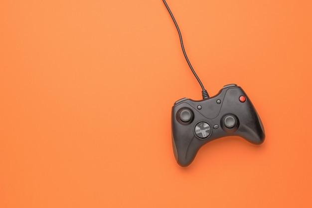 Una console di gioco su uno sfondo arancione brillante. disposizione piatta.