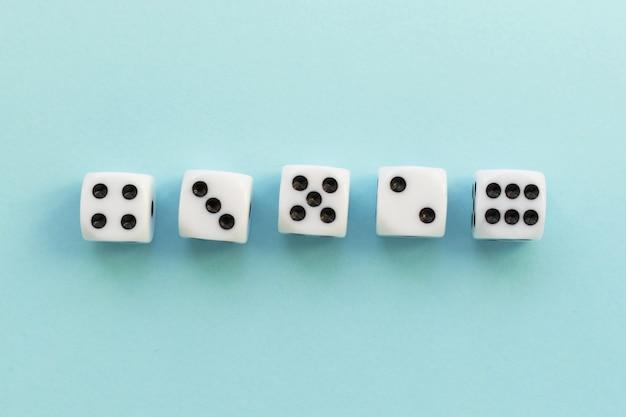 Dadi da gioco su sfondo blu. cubo da gioco con i numeri. articoli per giochi da tavolo. vista piatta e dall'alto con spazio di copia.