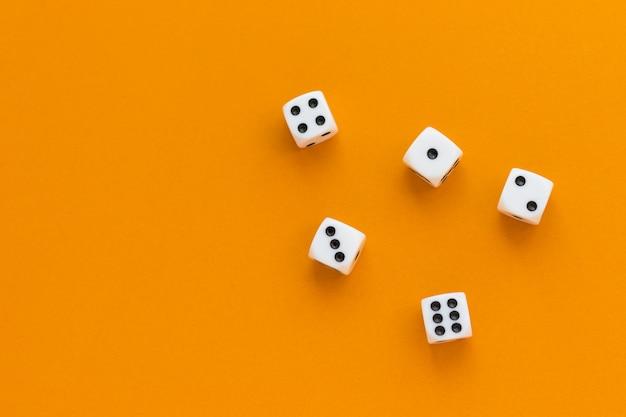 Dadi da gioco su sfondo arancione. cubo da gioco con i numeri. articoli per giochi da tavolo. vista piatta e dall'alto con spazio di copia.