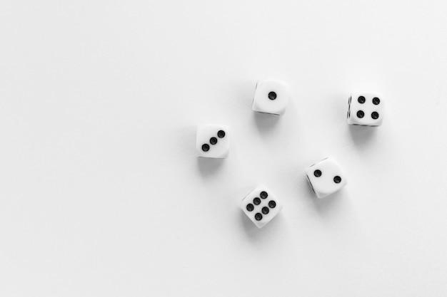 Dadi da gioco su sfondo bianco. cubo da gioco con i numeri. articoli per giochi da tavolo. vista piatta e dall'alto con spazio di copia.