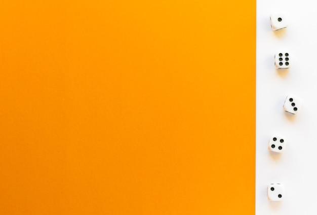 Dadi da gioco su sfondo bianco-arancio. cubo da gioco con i numeri. articoli per giochi da tavolo. vista piatta e dall'alto con spazio di copia.