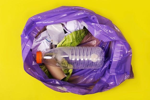 La spazzatura in un sacchetto su uno sfondo giallo