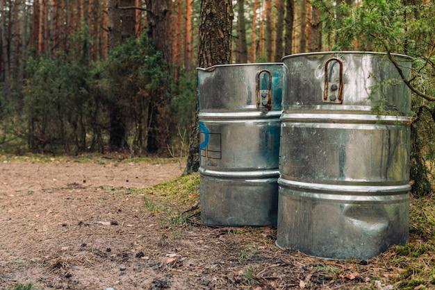Immondizia in grandi contenitori di metallo in natura, foresta, fiume come concetto di pulizie di primavera.